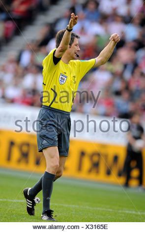 Referee Wolfgang Stark indicating to continue the game - Stock Photo