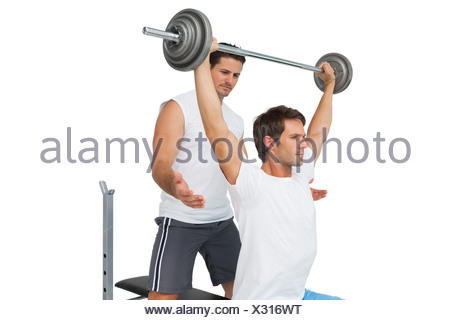 Trainer helping fit man to lift the barbell bench press - Stock Photo