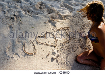 Woman writes I love you on the beach in Mexico. - Stock Photo