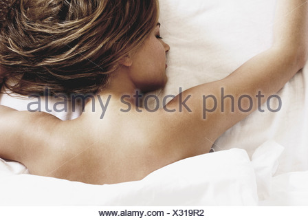 Young woman lying in bed sleeping - Stock Photo
