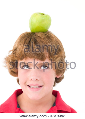 Young boy with apple on his head smiling - Stock Photo