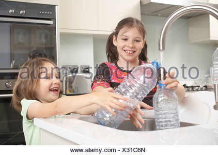 Girls filling up water bottle in kitchen - Stock Photo