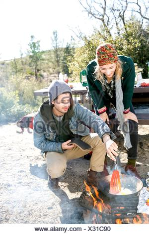 Young couple in rural setting, cooking food over camp-fire - Stock Photo