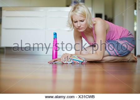 Frowning woman polishing wooden floor - Stock Photo