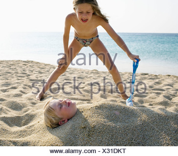 Young girl burying young boy in the sand at the beach . - Stock Photo