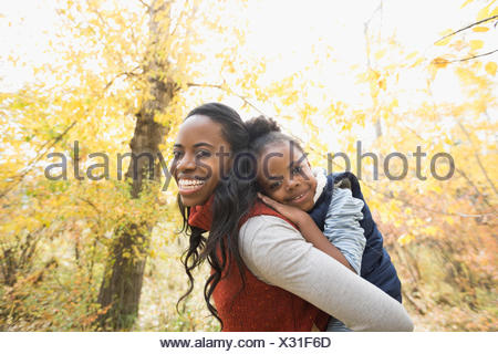 Portrait smiling mother piggybacking daughter in autumn woods - Stock Photo