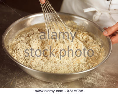 Closeup of baker's hands whisking batter with spelt flour in a bowl - Stock Photo
