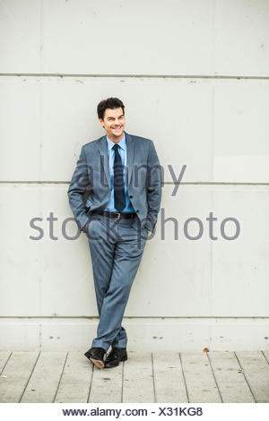 Portrait of smiling businessman wearing grey suit leaning against concrete wall - Stock Photo