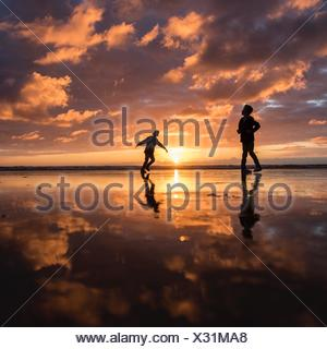 Silhouette of two boys playing on the beach at sunset - Stock Photo
