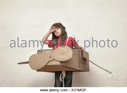 Little boy playing with pilot hat and cardboard box aeroplane - Stock Photo
