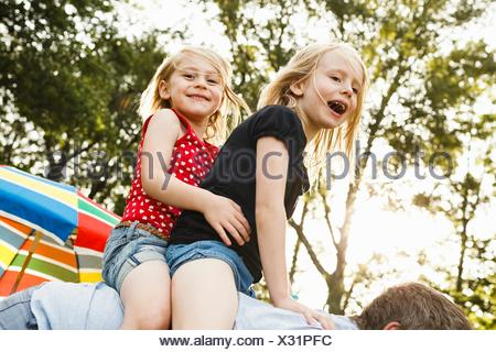 Mature man giving two young daughters piggy back in park - Stock Photo