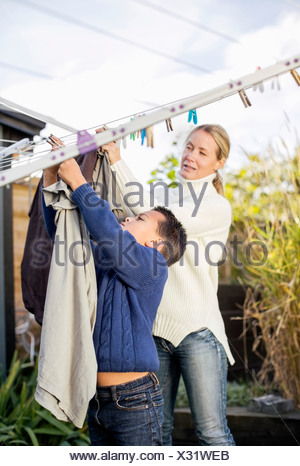 Mother and son drying laundry at yard - Stock Photo
