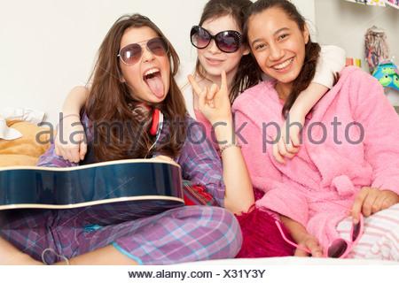 teenage girls laughing and playing music - Stock Photo