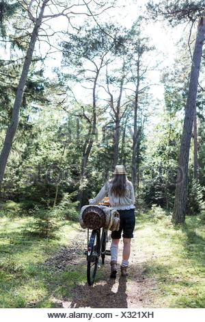 Mature woman pushing bicycle with foraging baskets on forest path - Stock Photo