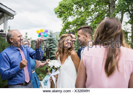 Wedding guests throwing confetti over bride and groom - Stock Photo