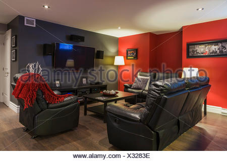 Black leather sofas and reclining chair with wooden coffee table in the family room  in the basement inside a contemporary country style residential home, Quebec, Canada - Stock Photo
