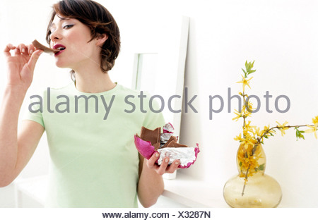 Female standing in living room holding up a half unwrapped foil wrapped chocolate Easter egg in one hand, and eating a piece - Stock Photo