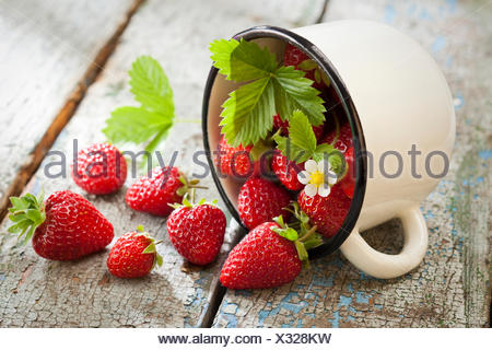 Strawberries in cup on wooden rustic background - Stock Photo