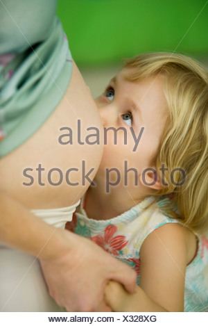 Little girl leaning against pregnant mother's belly - Stock Photo