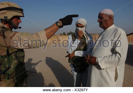 A Staff Sergeant of the 1st Squadron, 2nd Armored Cavalry Regiment talks to an Iraqi in whose home soldiers found two AK-47s, a pistol, and a bag of ammunition. - Stock Photo