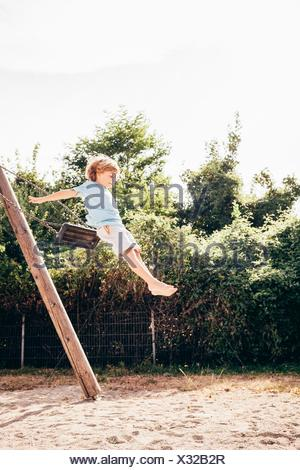 Side view of boy in mid air jumping from swing, Ulm, Baden Wuerttemberg, Germany