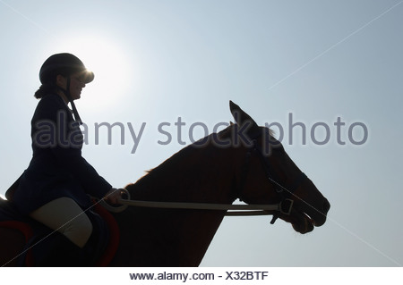 Silhouette of a female jockey riding a horse - Stock Photo