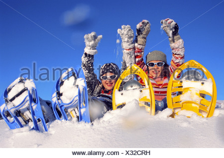 two girls with snowshoes, sitting in snow, wearing sun glasses, looking toward camera - Stock Photo