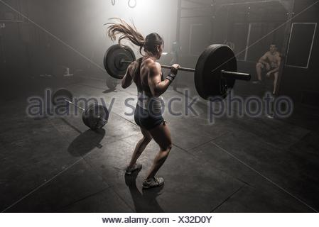 Young woman lifting barbell, rear view - Stock Photo
