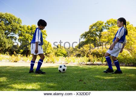 Cute football players playing football - Stock Photo