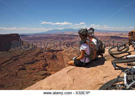 A mountain biking couple takes a break to enjoy the view from the edge of a cliff. - Stock Photo