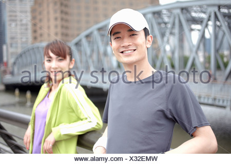 Male and female joggers by bridge - Stock Photo