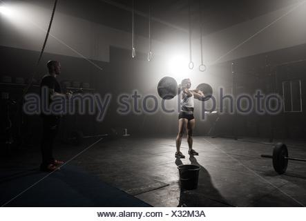 Young woman lifting barbell, while trainer looks on - Stock Photo