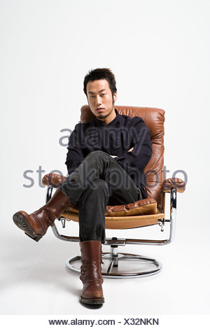 Japanese man sitting on a leather armchair - Stock Photo