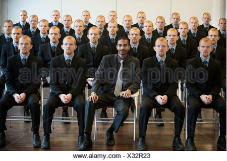 1 black businessman with 25 white clones - Stock Photo