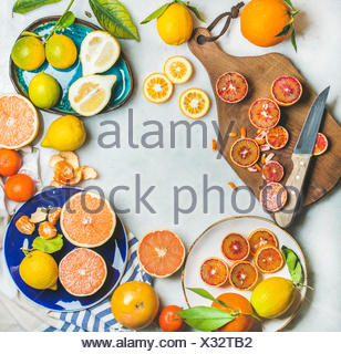 Natural fresh citrus fruits on wooden rustic board, colorful ceramic plates over grey marble table background, top view, copy space - Stock Photo