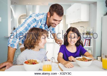 Happy man with children having breakfast - Stock Photo