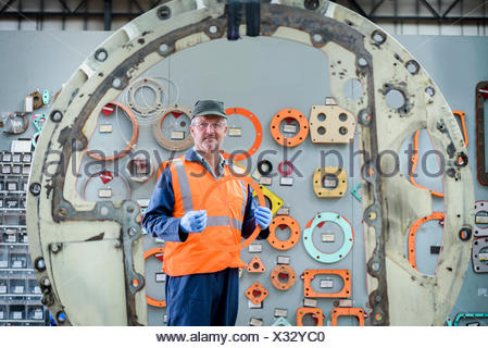 Portrait of locomotive engineer picking gaskets and seals in train works - Stock Photo