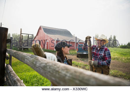 Ranchers with fence posts talking in pasture - Stock Photo