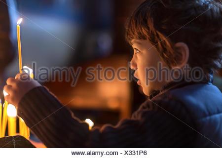 Bulgaria, Sofia, Young boy (4-5) holding candle - Stock Photo