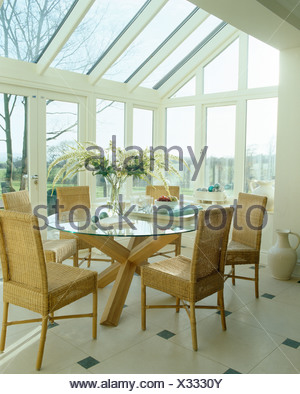 High-back wicker chairs and glass table in modern conservatory ...
