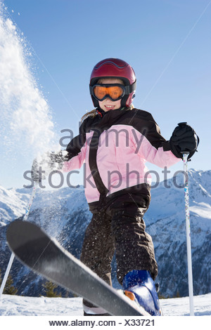 Young girl flicking snow off her skis - Stock Photo