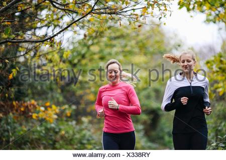 Teenage girl and woman running in park - Stock Photo