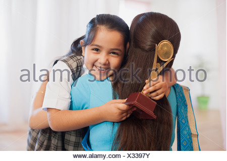 Woman hugging her daughter holding a trophy and smiling - Stock Photo