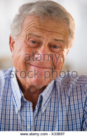 Portrait of senior man wearing button down shirt - Stock Photo