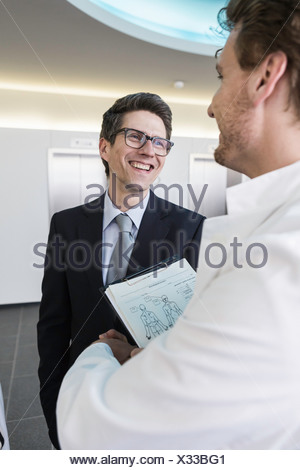 Man wearing lab coat, holding clipboard shaking hands with man wearing business attire - Stock Photo