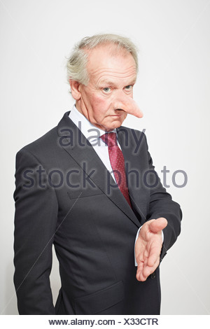 Businessman with long nose offering hand - Stock Photo