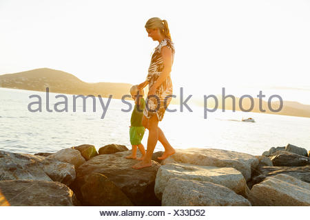 France, Provence-Alpes-Cote d´Azur, Saint Tropez, Woman walking with son along rocky coast at sunset - Stock Photo