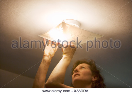 Woman repairing lighting fixture on ceiling - Stock Photo