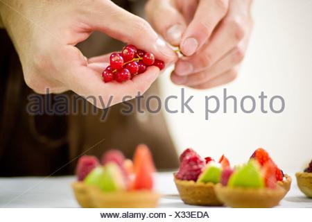 Baker making fruit tarts in kitchen - Stock Photo