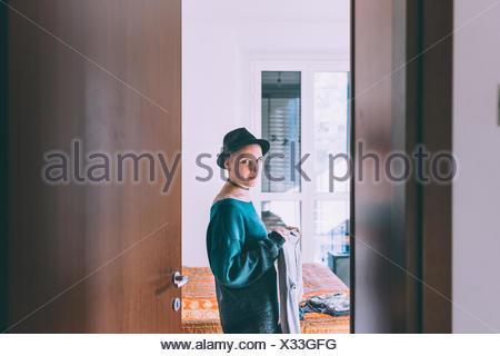 Doorway portrait of young woman wearing trilby standing in bedroom - Stock Photo